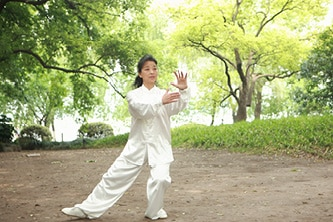 woman practicing tai chi outside in park learn taoist yoga